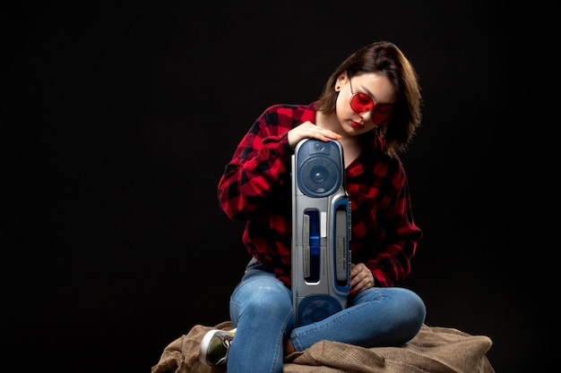 Una vista frontal joven y bella dama en camisa a cuadros rojo-negro en gafas de sol rojas con grabadora sentado