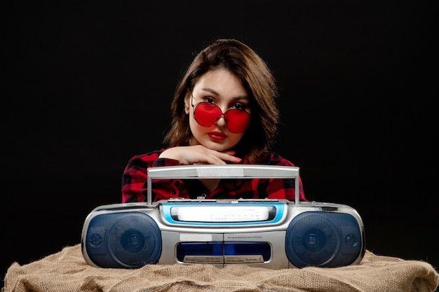 Una vista frontal joven y bella dama en camisa a cuadros rojo-negro con gafas de sol rojas posando con grabadora