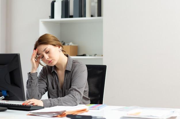 Una vista frontal joven y bella dama en camisa gris que trabaja con los documentos usando su pc sentado dentro de su oficina que sufre de un dolor de cabeza durante la actividad laboral del edificio durante el día