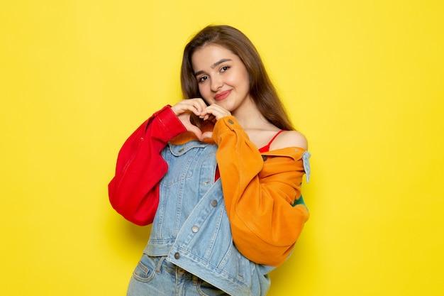 Una vista frontal joven y bella dama en camisa roja abrigo colorido y jeans azul que muestra el corazón signo modelo niña color hembra