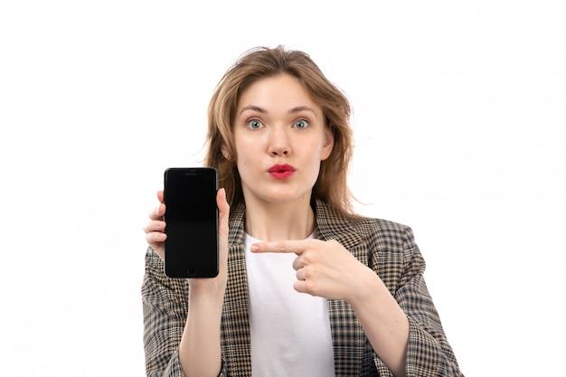 Una vista frontal joven bella dama en camiseta blanca jeans negros y abrigo sosteniendo mostrando smartphone sorprendido expresión en el blanco