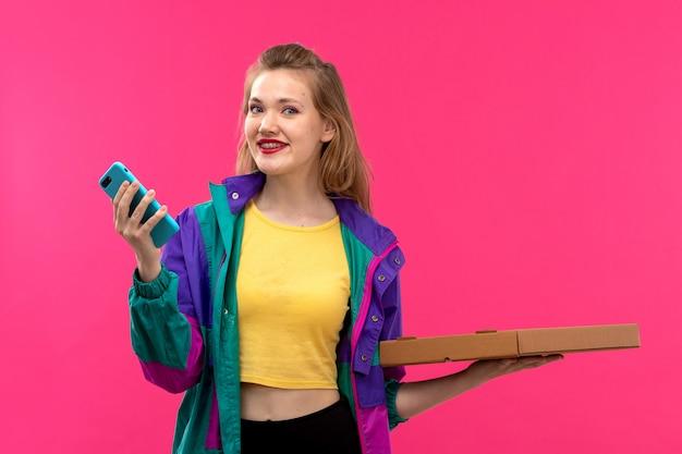 Una vista frontal joven y bella dama en chaqueta colorida camisa de color naranja pantalón negro sonriendo usando su teléfono con pizza