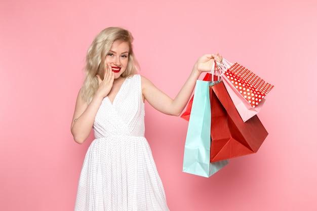 Una vista frontal joven y bella dama en vestido blanco con paquetes de compras con una sonrisa en su rostro