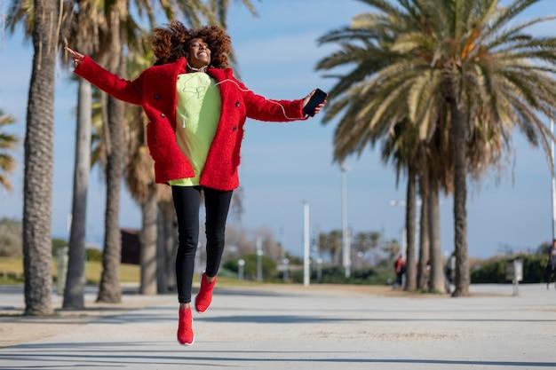 Vista frontal de la joven y bella mujer afroamericana rizada saltando y bailando mientras escucha música y sonriendo al aire libre