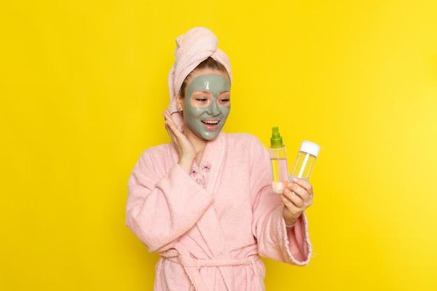 Una vista frontal joven y bella mujer en bata de baño rosa sosteniendo aerosoles sonriendo