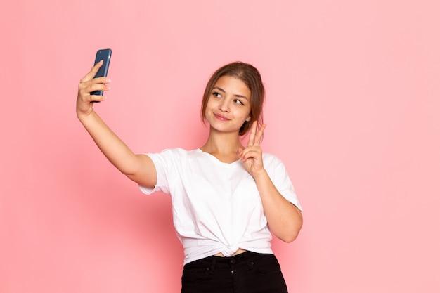 Una vista frontal joven y bella mujer en camisa blanca posando con expresión divertida y tomando una selfie