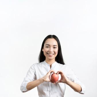 Vista frontal de la joven y bella mujer haciendo forma de corazón con manzana roja de pie sobre fondo blanco