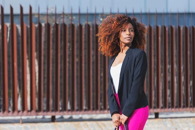 Vista frontal de la joven y bella mujer rizada con ropa elegante y bolso mientras está de pie en la calle en un día soleado