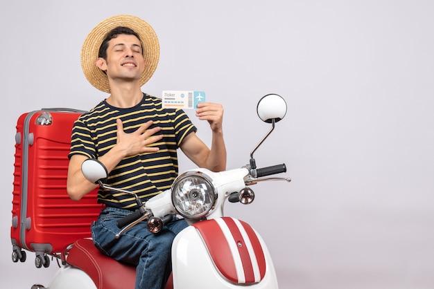 Vista frontal del joven bendecido con sombrero de paja en ciclomotor sosteniendo boleto de avión poniendo la mano sobre su pecho