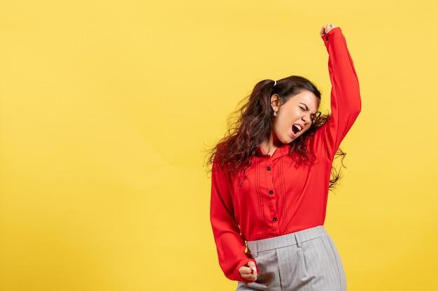 Vista frontal joven en blusa roja con cabello lindo bailando emocionalmente sobre fondo amarillo inocencia juvenil infantil color niño niña