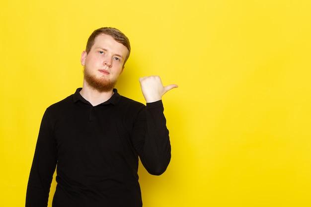 Vista frontal del joven en camisa negra posando