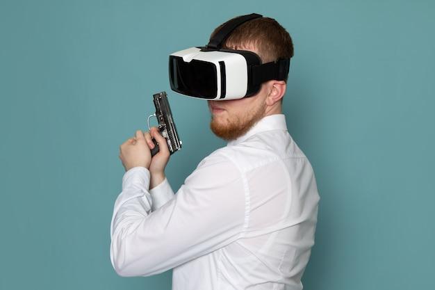 Una vista frontal joven en camiseta blanca con pistola jugando vr en el espacio azul