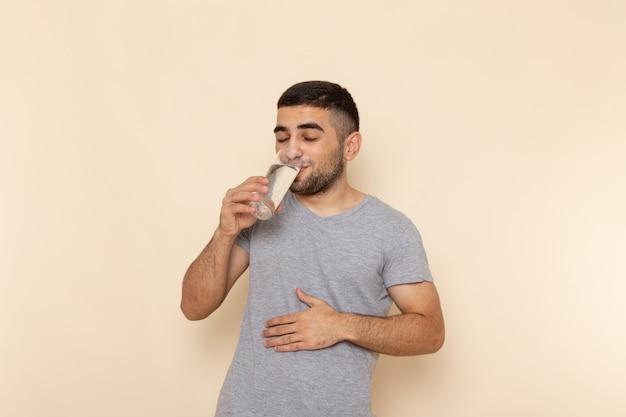 Vista frontal joven en camiseta gris vaso de agua en beige