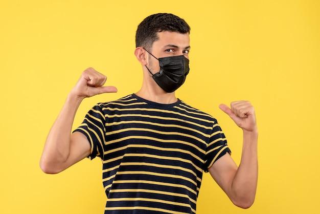 Vista frontal joven en camiseta a rayas blanco y negro apuntando a sí mismo fondo amarillo