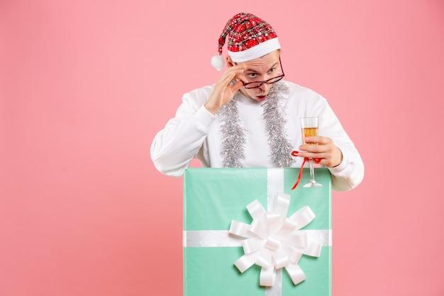 Vista frontal del joven celebrando la navidad con bebida y guirnaldas en la pared rosa.