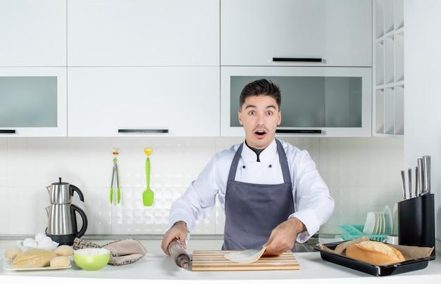 Vista frontal del joven chef de comis sorprendido en uniforme con soporte y preparando pasteles en la cocina blanca