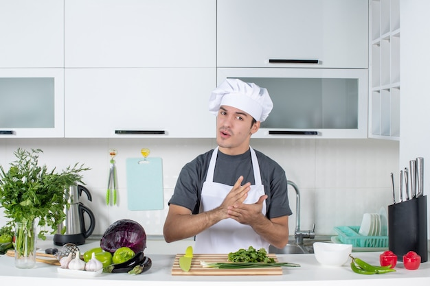 Vista frontal joven chef con delantal y gorro de cocinero