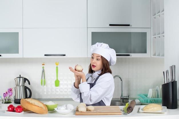 Vista frontal de la joven chef femenina concentrada en uniforme de pie detrás de la mesa preparando pasteles en la cocina blanca