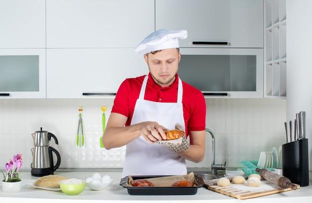 Vista frontal del joven chef masculino ocupado vistiendo titular sosteniendo uno de los pasteles recién horneados en la cocina blanca