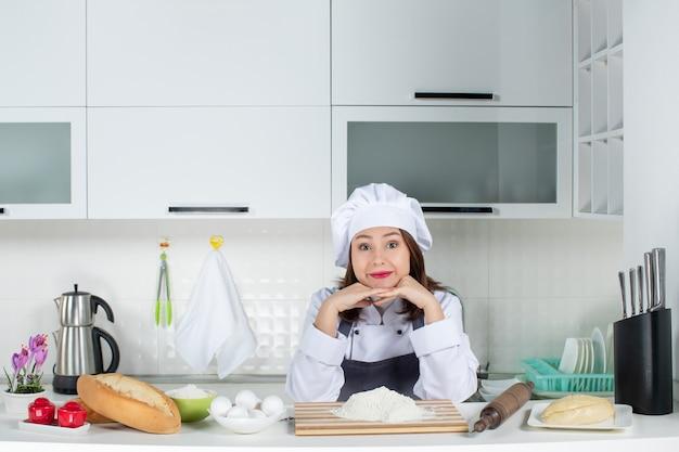 Vista frontal de la joven chef mujer sonriente en uniforme de pie detrás de la mesa con alimentos de tabla de cortar poniendo las manos debajo de la barbilla en la cocina blanca