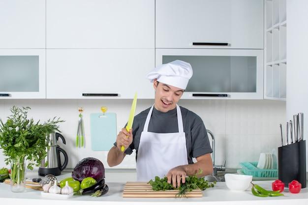 Vista frontal joven chef en uniforme disfrutando de cortar verduras