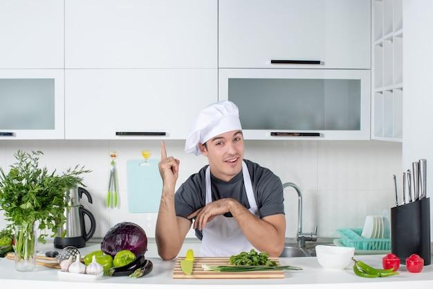 Vista frontal joven chef en verduras de corte uniforme en tabla de cortar