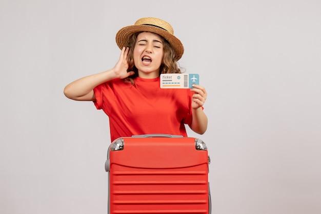 Vista frontal de la joven chica de vacaciones con su valija sosteniendo el boleto Foto gratis