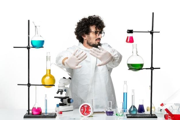 Vista frontal joven científico masculino en traje especial de pie alrededor de la mesa con soluciones en el escritorio blanco