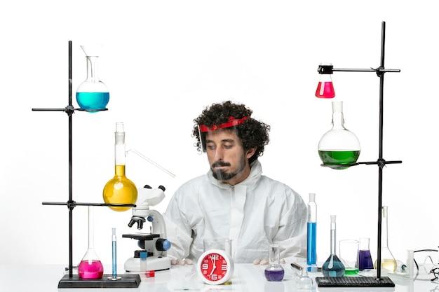 Vista frontal joven científico en traje especial y casco protector en una pared blanca