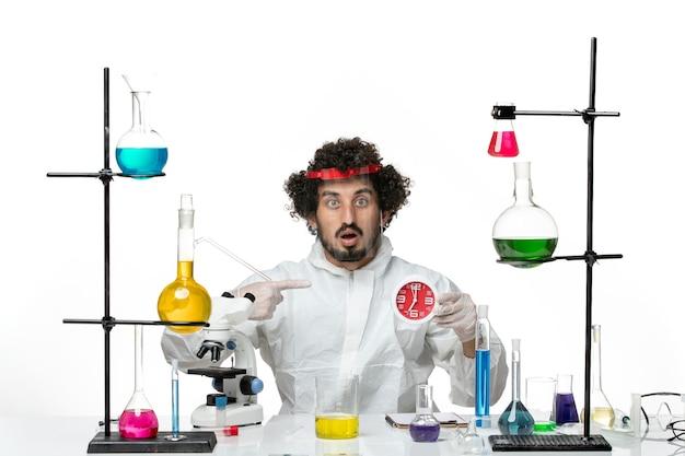 Vista frontal joven científico en traje especial con casco protector con reloj en pared blanca
