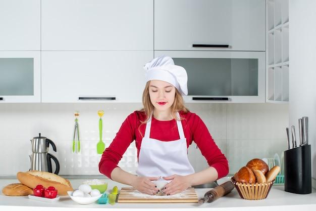Vista frontal joven cocinera amasando la masa en la tabla de cortar en la cocina