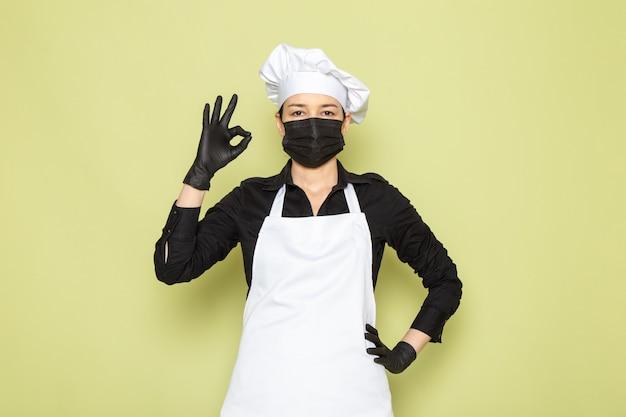 Una vista frontal joven cocinera en camisa negra capa de cocinero blanco gorra blanca posando en guantes negros máscara negra posando