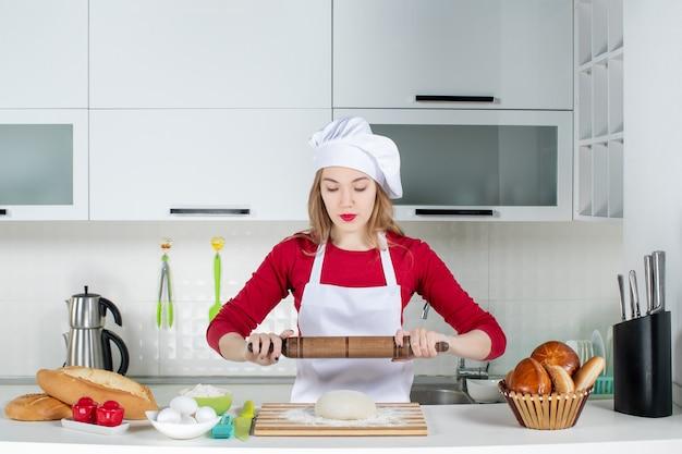 Vista frontal joven cocinera comenzando a enrollar la masa en la cocina