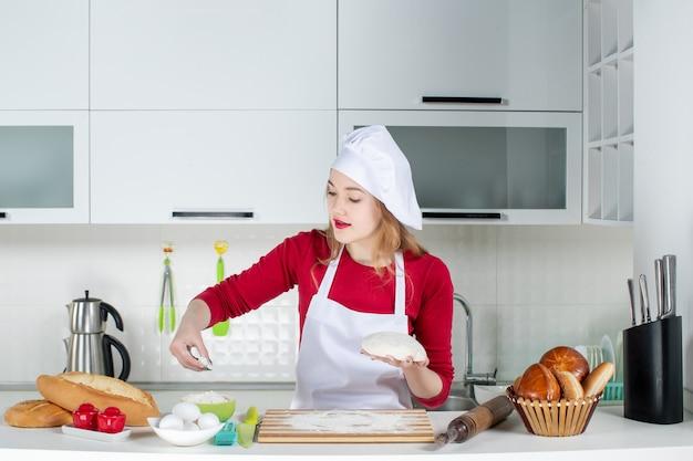 Vista frontal joven cocinera espolvorear harina a la tabla de cortar en la cocina