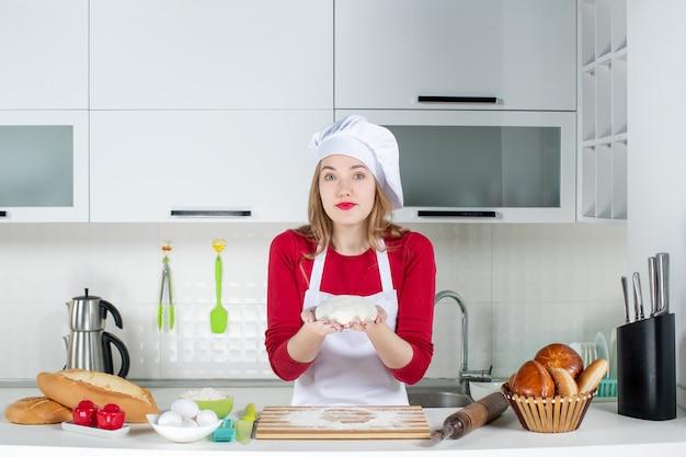 Vista frontal joven cocinera sosteniendo la masa en la cocina