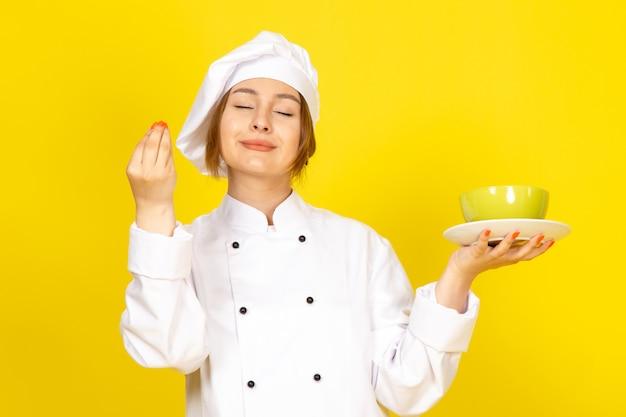 Una vista frontal joven cocinera en traje de cocinero blanco y gorra blanca con placas verdes y rojas encantadas en el amarillo