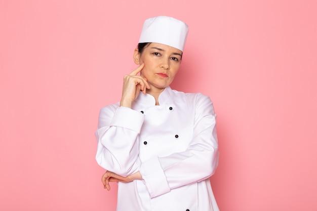 Una vista frontal joven cocinera en traje de cocinero blanco gorra blanca posando expresión de pensamiento profundo
