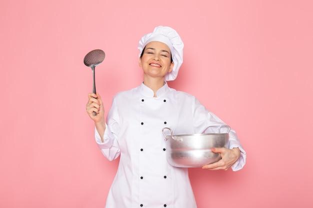 Una vista frontal joven cocinera en traje de cocinero blanco gorra blanca posando sosteniendo una cacerola de plata y una gran cuchara de plata sonriendo encantado