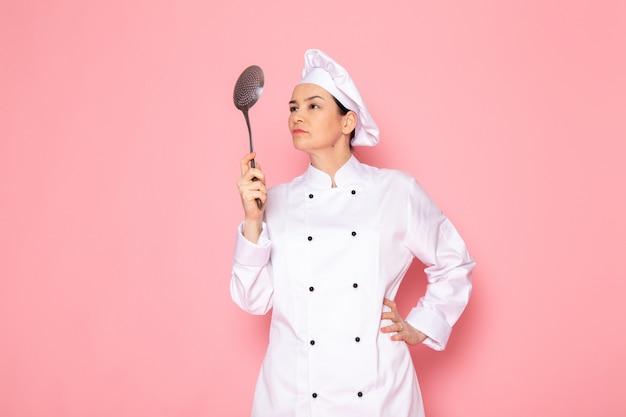 Una vista frontal joven cocinera en traje de cocinero blanco gorra blanca posando sosteniendo una gran cuchara de plata enojado preparándose para golpear