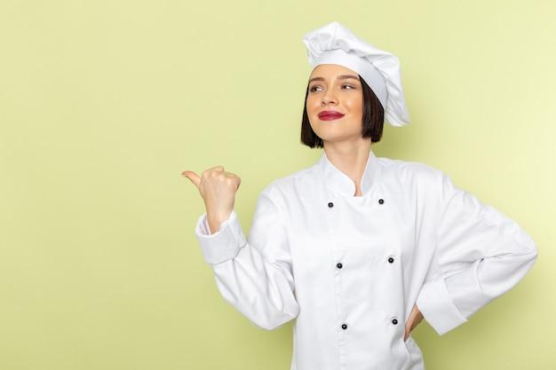 Una vista frontal joven cocinera en traje de cocinero blanco y gorra posando con una sonrisa en la pared verde dama trabajo color de la cocina de alimentos