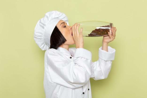 Vista frontal de una joven cocinera en traje de cocinero blanco y gorra sosteniendo un frasco con semillas de café en la pared verde trabajo de dama cocina color
