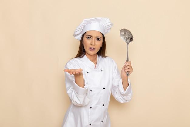 Vista frontal de la joven cocinera en traje de cocinero blanco sosteniendo una cuchara grande de plata en la pared blanca clara