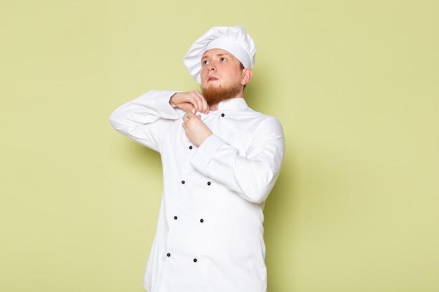Una vista frontal joven cocinero masculino en traje de cocinero blanco tapa de cabeza blanca arreglando su paño