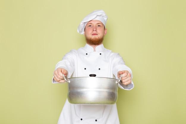 Una vista frontal joven cocinero masculino en traje de cocinero blanco tapa de cabeza blanca con una cacerola de plata