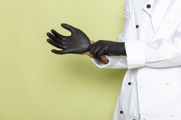 Vista frontal joven cocinero en traje de cocinero blanco con guantes oscuros en verde