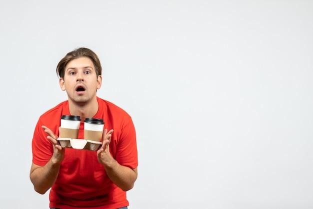 Vista frontal del joven concentrado en blusa roja sosteniendo café en vasos de papel sobre fondo blanco.