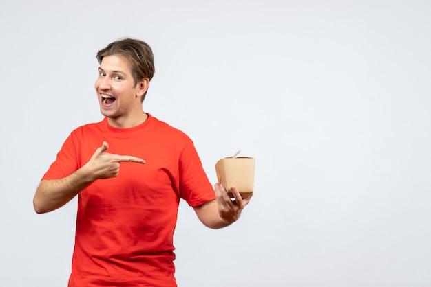Vista frontal del joven confiado en blusa roja apuntando caja pequeña sobre fondo blanco.