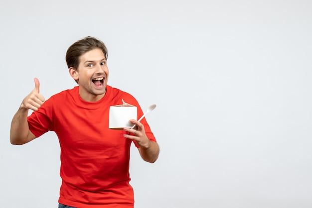 Vista frontal del joven confiado en blusa roja sosteniendo una caja de papel y haciendo un gesto de ok sobre fondo blanco.
