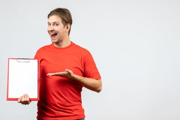 Vista frontal del joven confiado en blusa roja sosteniendo documento sobre fondo blanco.