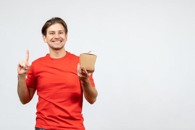 Vista frontal del joven confiado en blusa roja sosteniendo una pequeña caja y apuntando hacia arriba sobre fondo blanco.
